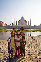Smiling children  standing on the bank of river Yamuna and Taj Mahal in the background. (Photo by Matt Considine - Images of Asia Collection)