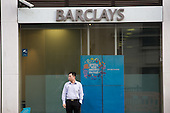 A man smokes outside a branch of Barclays Bank in central London.