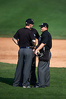 Umpires Max Guyll, Nick Lentz and Seth Buckminster discuss a call during a game between the Indianapolis Indians and Rochester Red Wings on June 10, 2015 at Frontier Field in Rochester, New York.  Indianapolis defeated Rochester 5-3.  (Mike Janes/Four Seam Images)