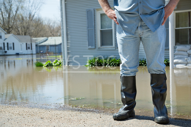 Man standing with arms akimbo looking at flooded street