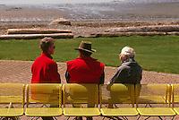 Three Senior People sitting on a Bench along Seaside Promenade Walkway and Semiahmoo Bay, White Rock, BC, British Columbia, Canada