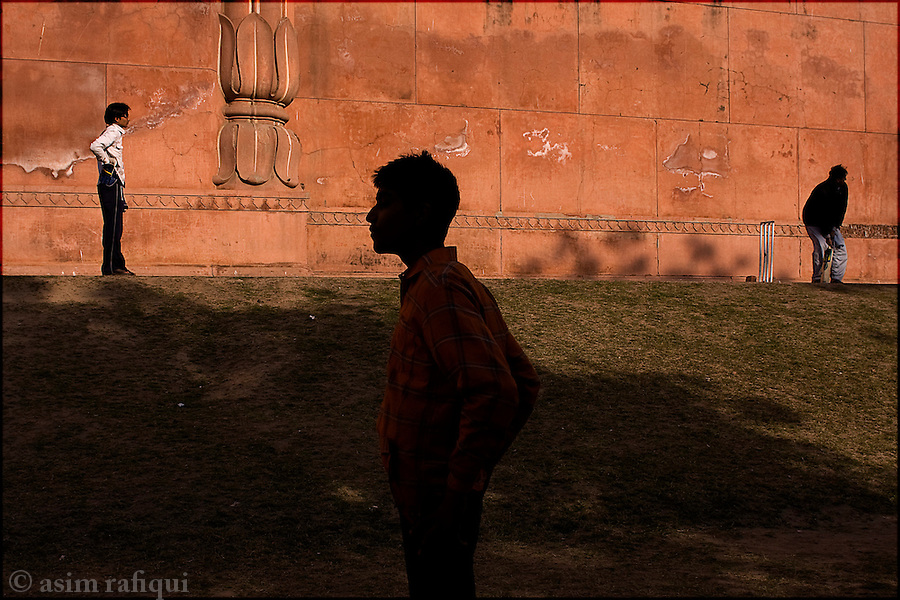 playing cricket, considered the national sport, along the ancient walls of the grand badshami mosque in the old city of lahore