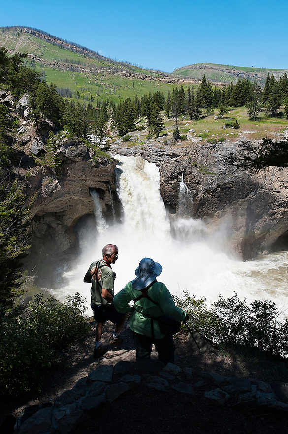 Two hikers take in the view of Natural Bridge Falls during high water near McLeod, Montana.