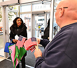 Jim Walker (right) with the Belleville Exchange Club offers a small American flag to St. Clair County Circuit Clerk Kahalah Clay as she folds up her umbrella after entering city hall. The city of Belleville held their 21st annual Veterans Day ceremony inside Belleville City Hall on Thursday November 11, 2019. It was moved inside due to the winter weather.<br /> Photo by Tim Vizer