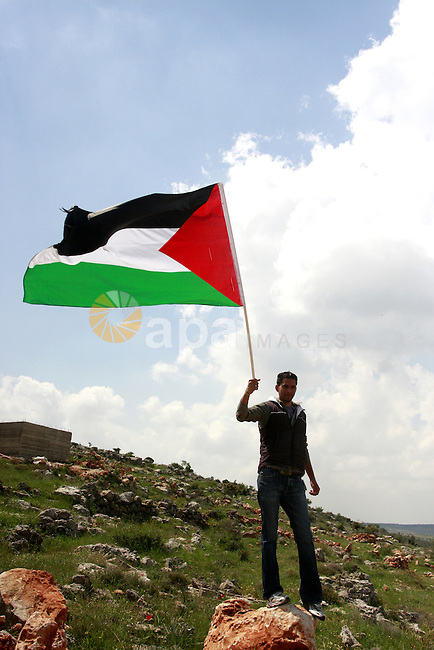 A Palestinian youth carries national flag to mark the anniversary of Land Day in the village of Kafr al-Dik in the Nablus region of the West Bank on March 29, 2012. Land Day recalls an incident in 1976 when Israeli troops shot and killed six people during protests against land confiscations.  Photo by Wagdi Eshtayah