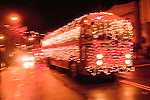 Festive school bus with Christmas lights in Sutter Creek's annual Parade of Lights Christmas parade downtown on a rainy night in the  Mother Lode of Calif.