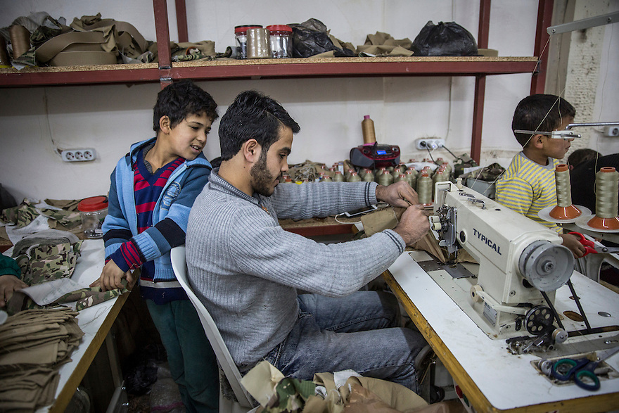 ANTAKYA, TURKEY-- Feb 12. 2016-- Employees at work in a shop that makes backpacks, uniforms and other military gear for the Syrian market.