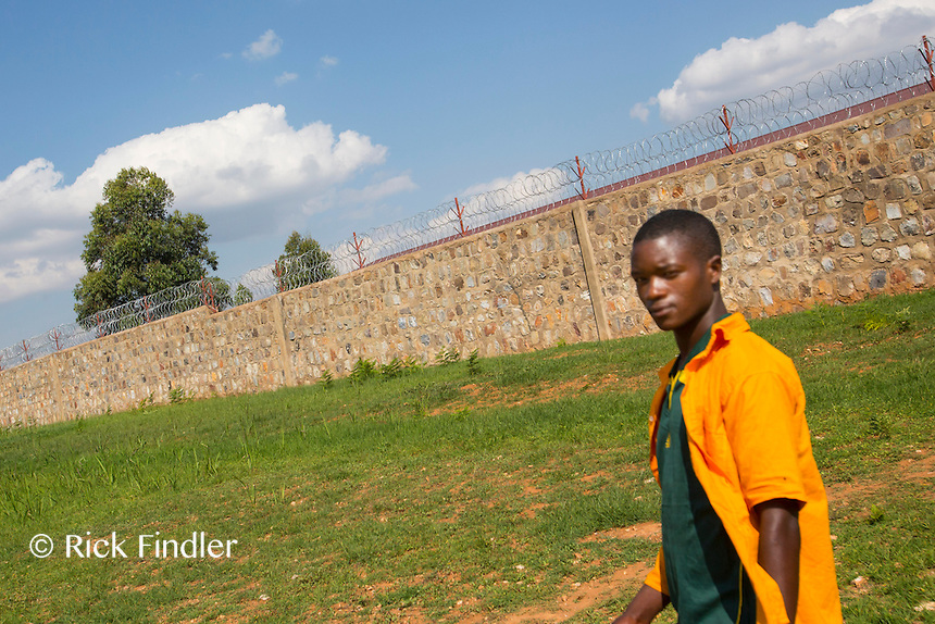BURUNDI, Ruyigi: 10 June 2015 Ruyigi Re-education Centre Feature.<br /> See accompanying article for general information. <br /> Pictured: An inmate walks infant of the 10 foot barbed-wire inner wall of the re-education centre. <br /> Rick Findler / Story Picture Agency