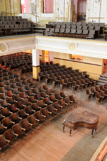 Empty concert hall or high school auditorium with old grand piano and wooden seats, very bad condition.