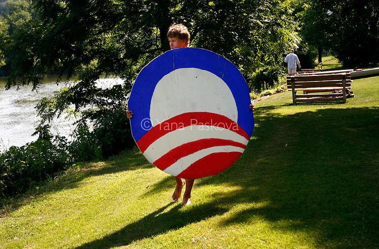 A boy carries the campaign logo of Democratic Presidential hopeful Barack Obama (D-IL), as he speaks in Manchester, IA, on July 14, 2007.
