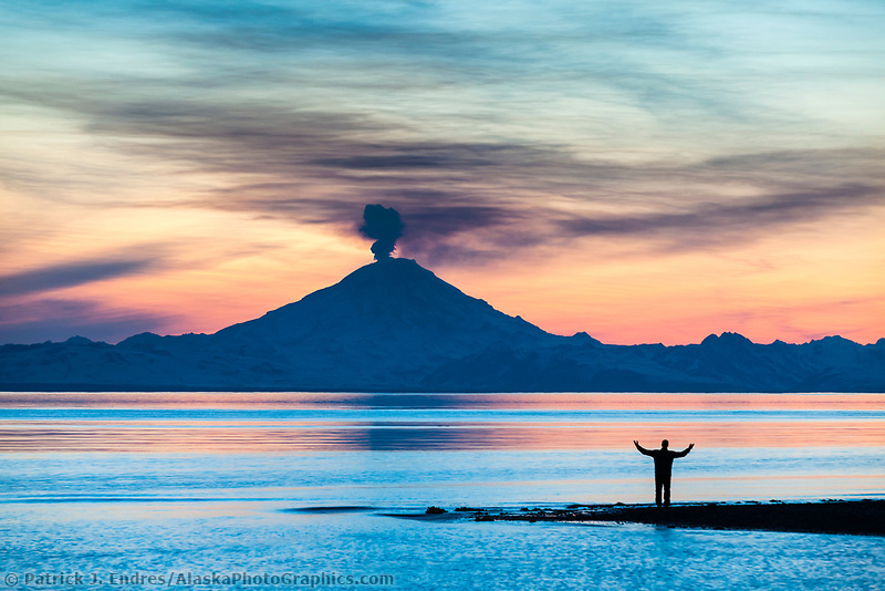 Man watches the plume of gas and vapor vent from the summit of Mt. Redoubt volcano (10,191 ft), of the Chigmit mountains, Aleutian range. View across Cook Inlet approximately 50 miles, at sunset, southcentral, Alaska.