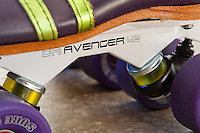 A closeup of the Sure-Grip Magnesium (white) Avenger DA 45 plate that's mounted onto Michelle's custom (ColorLab) 495 boot in purple and metallic lime green.  The cushions are the SureGrip yellows, and the wheels are purple Sure Grip Fames.
