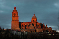 Low angle view, Cathedral, Salamanca, Spain, pictured on December 19, 2010 lit by the evening sun. Salamanca, Spain's most important University city,  has two adjoining Cathedrals, Old and New. The old Romanesque Cathedral was begun in the 12th century, and the new in the 16th century. Its style was designed to be Gothic rather than Renaissance in keeping with its older neighbour, but building continued over several centuries and a Baroque cupola was added in the 18th century. Restoration was necessary after the great Lisbon earthquake, 1755. Picture by Manuel Cohen