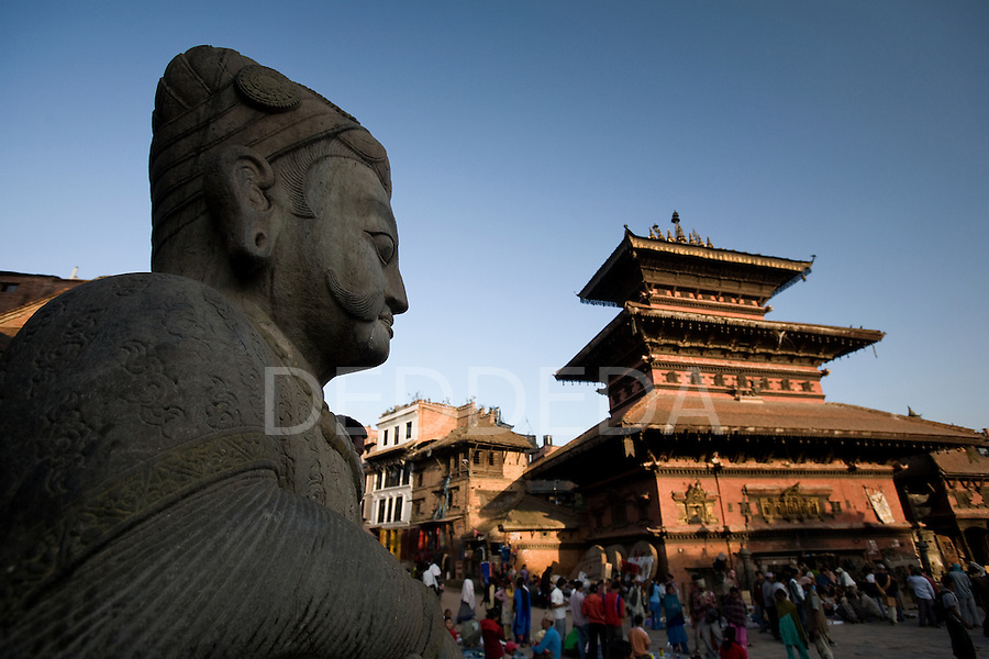 A stone statue and historic buildings in the ancient city of Bhaktapur Durbar Square, Nepal, an UNESCO World Heritage Site.