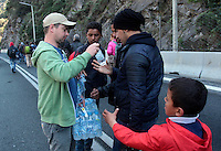 Pictured: Migrants are given bottles of water on the motorway Thursday 25 February 2016<br /> Re: Hundreds of migrants, including families with young children, that were stranded at Tempe in central Greece, were forced to walk on foot on the motorway to reach Idomen, about 168 kilometres away, in the northern part of the country, at the Greek FYRO Macedonian border. Local police were at first escorting them, then made sure that they were safely transported on coaches.