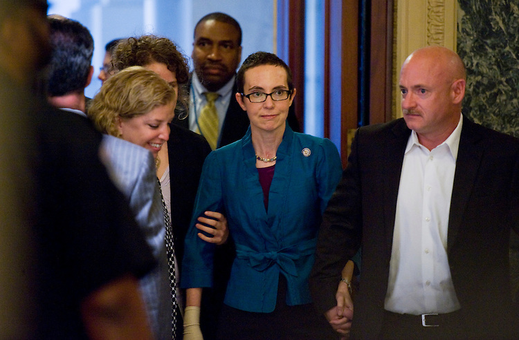 UNITED STATES - AUGUST 01: Rep. Gabrielle Giffords, D-Ariz., arrives to the Capitol with her husband Mark Kelly and Rep. Debbie Wasserman Schultz, D-Fla., to vote on the debt limit bill in the House, Monday.  Giffords has been recovering from a gunshot wound to the head sustained January 8th in Tucson.  (Photo By Tom Williams/Roll Call)