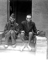 These two staring, emaciated men are liberated inmates of Lager Nordhausen, a Gestapo concentration camp.  The camp had from 3,000 to 4,000 inmates.  All were maltreated, beaten and starved.  Germany, April 12, 1945.  T4c. James E. Myers. (Army)<br /> NARA FILE #:  111-SC-203416<br /> WAR & CONFLICT BOOK #:  1104