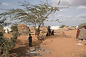 Kenya - Dadaab. A family of Somali refugees standing next to their tent in ifo camp.