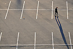 Man taking a short cut through a parking lot, Spokane, Washington
