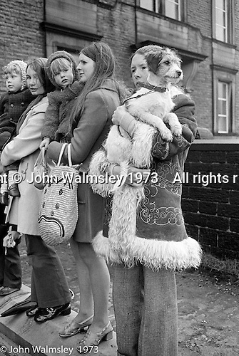 "Watching the ""Nutters' Dance"", Bacup, Lancashire  1973.  The ""Nutters' Dance"", Bacup, Lancashire  1973.  On Easter Saturday every year the ""Coco-nut"" dancers gather at one boundary of the town and dance their way across to the other accompanied by members of the Stackstead Silver Band, collecting for charity as they go.  It includes a short stop in one of the pubs."