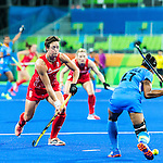 Sushila Pukhrambam #27 of India prepares to hit while Hannah Macleod #6 of Great Britain moves in during India vs Great Britain in a Pool B game at the Rio 2016 Olympics at the Olympic Hockey Centre in Rio de Janeiro, Brazil.