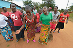 Members of a youth sexual and reproductive health club educate their peers using song and dance outside a Catholic church in Kacheche, Malawi. With assistance from the AIDS program of the Livingstonia Synod of the Church of Central Africa Presbyterian, club members educate their peers about avoiding HIV transmission, resisting early marriages, and the prevention of school dropouts.