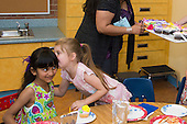 MR / Schenectady, NY. Zoller Elementary School (urban public school). Kindergarten classroom. Student (girl, 5) whispers to her friend (girl, 6, biracial) at classroom birthday party. MR: Myk2, Stu1. ID: AM-gKw. © Ellen B. Senisi.