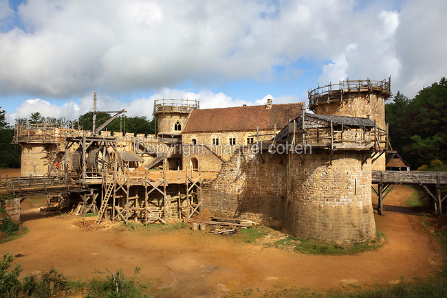 North Range or Logis Seigneurial in the centre, completed 2010, with Corner Towers and Great Tower or Tour Maitresse on the right, still under construction, lifting gear or squirrel cage with double drum, and footbridges over the moat trench, at the Chateau de Guedelon, a castle built since 1997 using only medieval materials and processes, photographed in 2017, in Treigny, Yonne, Burgundy, France. The Guedelon project was begun in 1997 by Michel Guyot, owner of the nearby Chateau de Saint-Fargeau, with architect Jacques Moulin. It is an educational and scientific project with the aim of understanding medieval building techniques and the chateau should be completed in the 2020s. Picture by Manuel Cohen