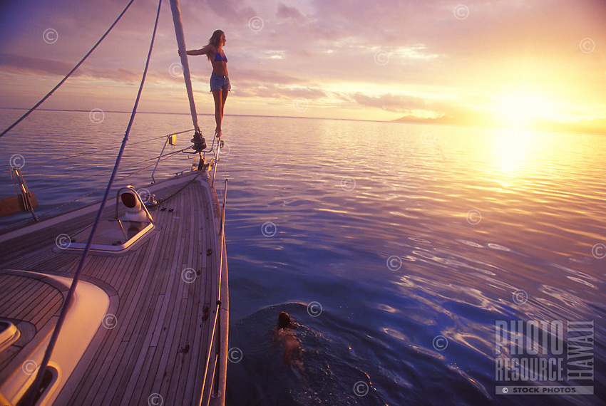 Mother and daughet having a sunset swim aboard yacht 'Heron', anchored off Tahiti, with Moorea in background, French Polynesia