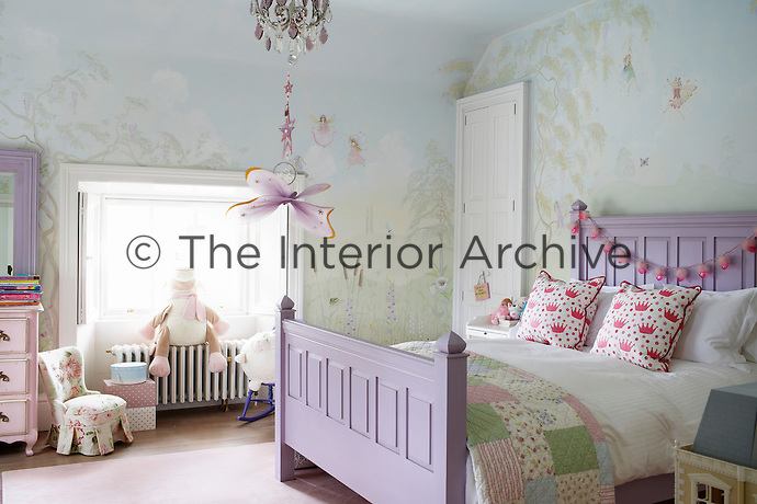 A child's pretty bedroom with a fairy mural painted on the walls. A lavender painted bed has a patchwork quilt cover.