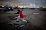 Ten-year-old Benito Tirjeron jumps over a puddle on the edge of the Parklawn neighborhood in Modesto, Calif., March 1, 2012.