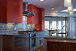 Contemporary kitchen with glass tile backsplash and granite island.