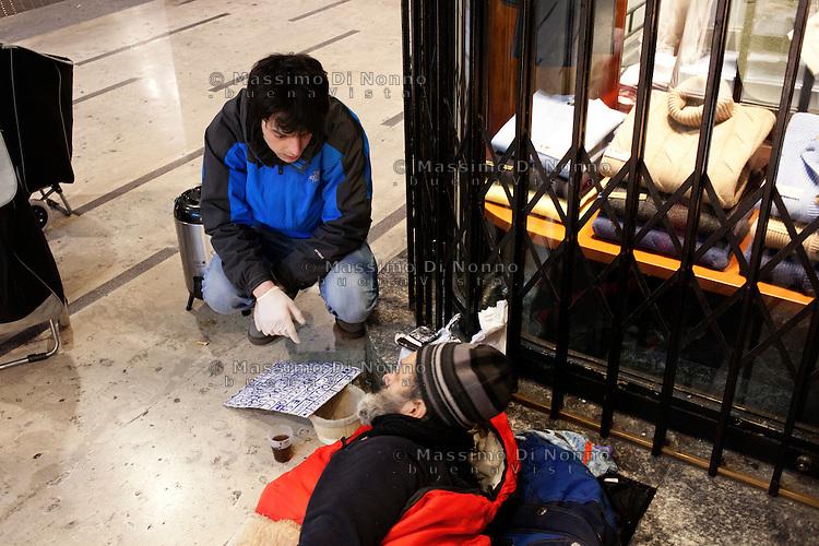 Milano: un volontario del progetto Arca assiste un clochard nel centro di Milano durante i giorni di grande freddo.