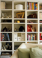 Wall-to-wall shelving in the living room displays a collection of books, vintage shoes and other period objects