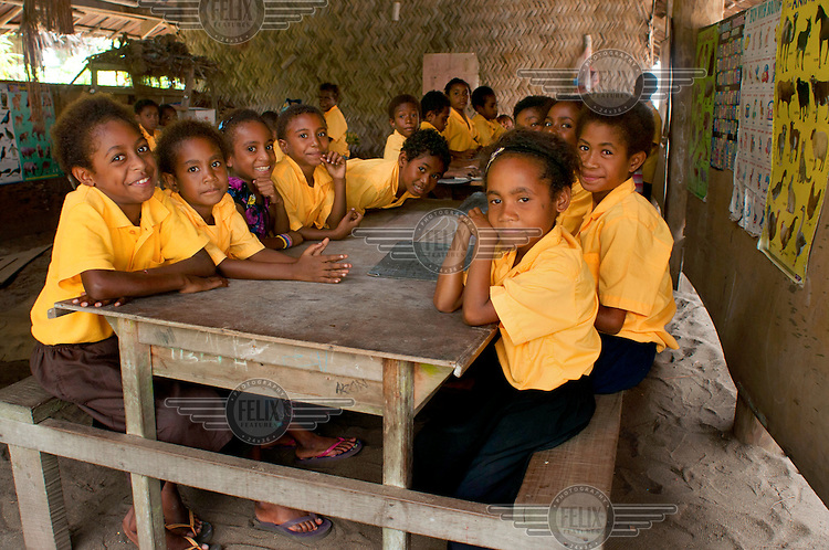 Children sit around a table in the primary school, built on the beach in Labu Tale village.