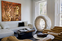 Tiered modular sofas in the living room are teamed with a contemporary banquette, an iconic Verner Panton 1974 Sitting Wheel and a copper artwork by Lucio Fontana