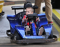 NWA Media/Michael Woods --12/20/2014-- w @NWAMICHAELW...Mason Locke, age 3 from Springdale, rides in a go-cart with his Mickey Mouse toy Saturday morning at Lokomotion Family Fun Center during the Springdale firefighters annual Christmas event for less fortunate children.  Springdale firefighters treated local kids with food, rides, games, and gifts from Santa during their annual event.