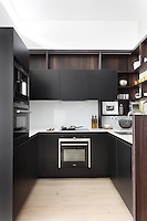 A modern galley kitchen with dark grey units and wooden floor.