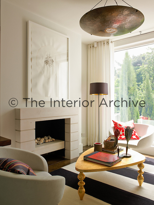 A contemporary watercolour hangs above the modern stone fireplace in the living room
