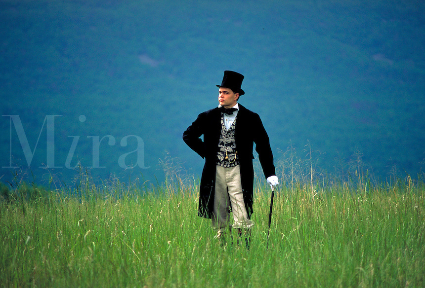 A young man poses leaning on a stylish walking cane while standing amidst tall green grass in the New Market Battlefield. He is clad in Civil War period costume consisting in black coat, tan britches and top hat. New Market Virginia, New Market Battlefiel