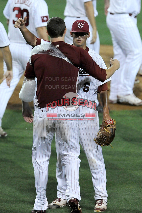 Starting pitcher Jordan Montgomery (34), with arm iced down, congratulates closer Joel Seddon (6) of the South Carolina Gamecocks after the final out in an NCAA Division I Baseball Regional Tournament game against the Campbell Camels on Friday, May 30, 2014, at Carolina Stadium in Columbia, South Carolina. South Carolina won, 5-2. (Tom Priddy/Four Seam Images)