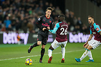 Arthur Masuaku of West Ham United holds back Mesut Ozil of Arsenal during the Premier League match between West Ham United and Arsenal at the Olympic Park, London, England on 13 December 2017. Photo by Andy Rowland.