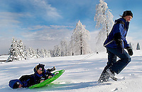 A woman pulls her son's on a sled in the deep snow.