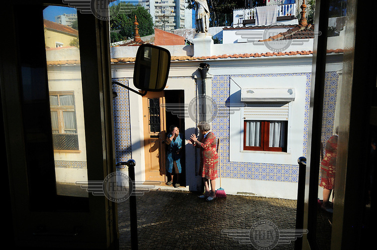 Two women chat in the doorway of a house, seen from one of Porto's historic trams. This tram is part of a recently restored heritage network of three lines.