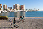 People cycling along the waterfront by the marina area, Malaga, Spain