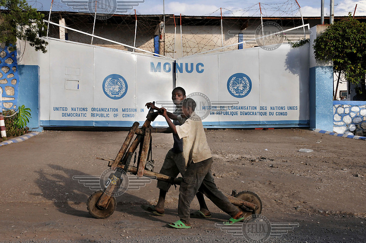 Kids on a wooden transport bike in front of the headquarters of the United Nations (UN) mission in Congo (MONUC). .