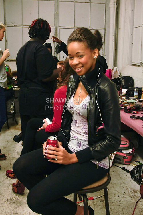 Model smiles holding a soda, backstage during BK Fashion Weekend Spring Summer 2012.