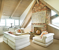 Comfortable modular seating is arranged around a fireplace in the light-filled top floor sitting room