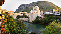 Sunset late afternoon light. View along the river of the old reconstructed bridge. Restaurants cafes along the river bed. Historic town of Mostar. Federation Bosne i Hercegovine. Bosnia Herzegovina, Europe.