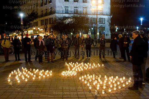 Activists and supporters light candles forming a large nuclear symbol remembering the victims of the catastrophe at Fukushima and to demonstrate the need for alternative energy sources in Budapest, Hungary on March 11, 2012. ATTILA VOLGYI